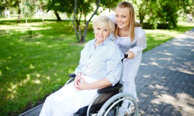 Female caregiver walking with senior patient in park